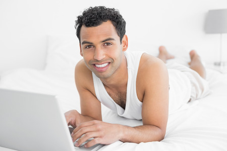 Portrait of a smiling casual young man using laptop in bed at home photo