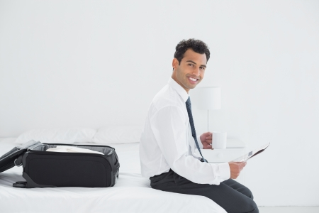 Smiling young businessman with coffee cup reading newspaper by luggage at a hotel room photo