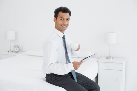 Portrait of a smiling young businessman with coffee cup reading newspaper at a hotel room photo