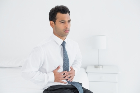 dolor de estomago: Hombre de negocios joven con dolor de est�mago sentado en la cama en su casa
