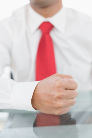 outraged: Close-up mid section of a well dressed businessman with clenched fist on the desk at office Stock Photo