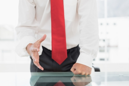 Close-up mid section of a well dressed businessman with clenched fist on the desk at office photo