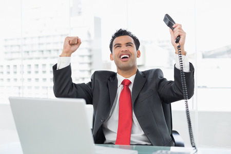 Elegant businessman cheering with telephone receiver in front of laptop at office desk photo
