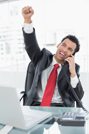 Elegant businessman cheering while on call in front of laptop at office desk photo