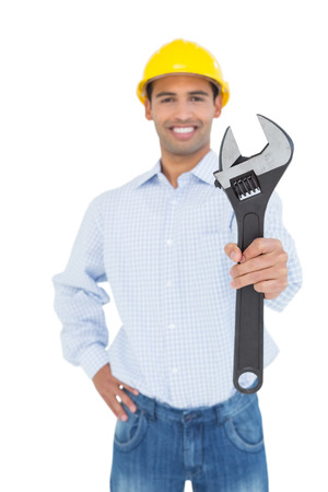 Portrait of a smiling young handyman holding out a wrench against white background photo