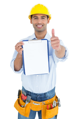 Portrait of a smiling handyman in yellow hard hat with clipboard gesturing thumbs up against white background photo