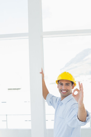 Portrait of a smiling handyman in yellow hard hat gesturing okay sign in a bright office photo