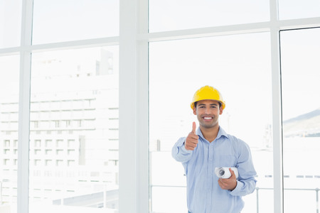 Portrait of a smiling architect in yellow hard hat with blueprint gesturing thumbs up in a bright office photo