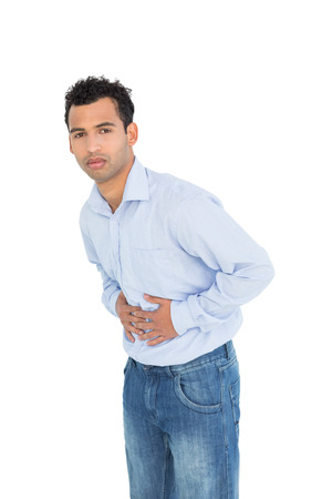 Portrait of a casual young man with stomach pain standing against white background