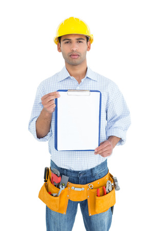 Portrait of a handyman in yellow hard hat holding a clipboard against white background photo