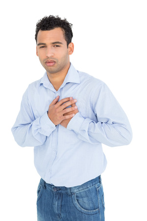 Portrait of a casual young man with chest pain standing against white background photo