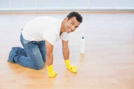 Side view portrait a smiling young man cleaning the parquet floor at house photo
