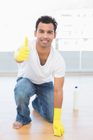 Portrait of a smiling young man cleaning the floor while gesturing okay sign at house photo
