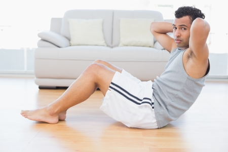 Side view portrait of a young man doing abdominal crunches in the living room at house Stock Photo