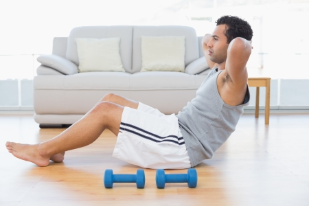 Side view of a young man doing abdominal crunches in the living room at house Stock Photo