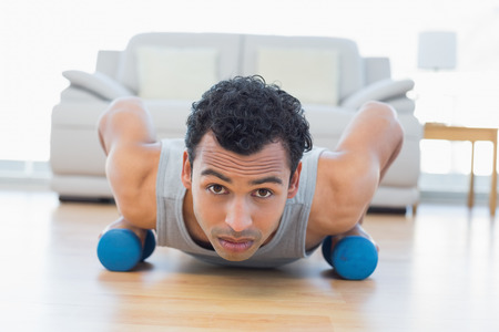 Portrait of a sporty young man with dumbbells doing push ups in the living room at house photo