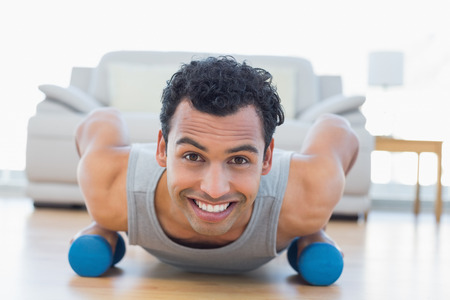 Portrait of a smiling young man with dumbbells doing push ups in the living room at house photo