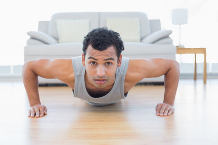 Portrait of a sporty young man doing push ups in the living room at house photo