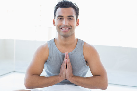 manos unidas: Retrato de un hombre joven y sonriente sentado con las manos juntas contra el fondo brillante