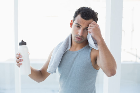 Portrait of a young man wiping sweat with towel in a bright fitness studio photo
