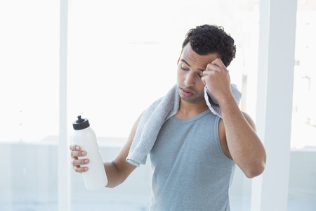 Tired young man wiping sweat with towel in a bright fitness studio photo