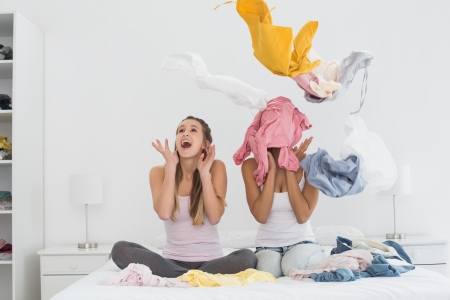 Two surprised pretty female friends with clothes up on bed at home photo