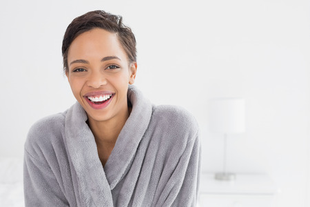 Portrait of a happy young female in bathrobe standing at home photo