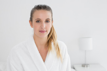 Portrait of a pretty young female in bathrobe sitting on bed at home photo
