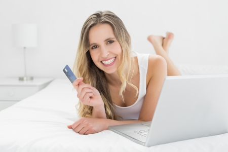 Casual young woman doing online shopping through laptop and credit card in bed photo