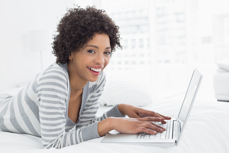 Side view portrait of a smiling young woman using laptop in bed at home photo