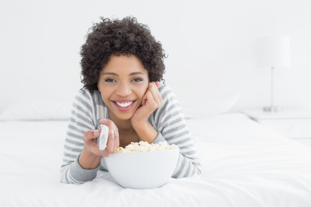 Portrait of a smiling young woman with remote control and popcorn bowl lying in bed at home photo