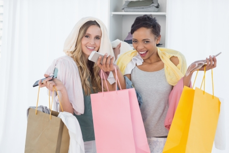 Portrait of two smiling young women standing with shopping bags at home photo