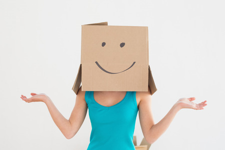 Casual young woman in blue tank top with smiley cardboard box over face in a new house photo