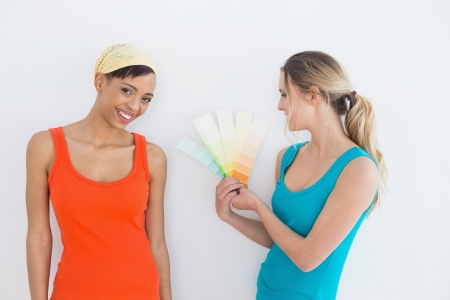 Portrait of two female friends choosing color for painting a room against white background photo