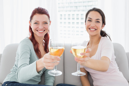 Portrait of two happy young female friends holding out wine glasses on sofa at home photo
