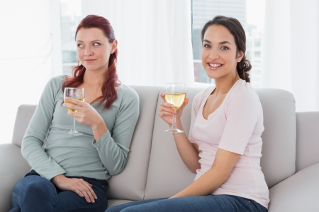 Two young female friends with wine glasses sitting on sofa at home photo