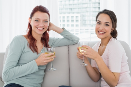 Portrait of two young female friends with wine glasses sitting on sofa at home photo