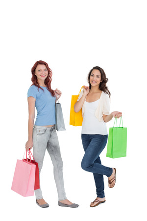 Full length portrait of two happy young female friends with shopping bags over white background photo