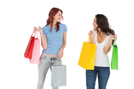 Two happy young female friends with shopping bags over white background photo
