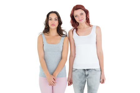 Portrait of two female friends standing over white background photo