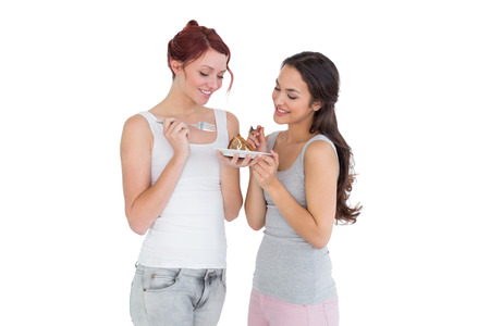 Two happy young female friends eating pastry together over white background photo