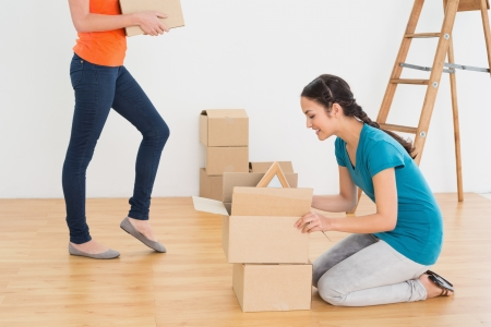 unwrapping: Two friends moving together in a new house and unwrapping boxes