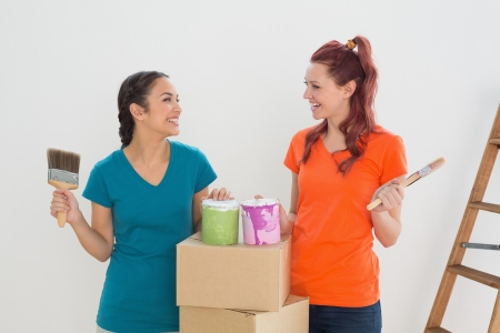 Two cheerful female friends holding paint brushes with cans and boxes in a new house photo