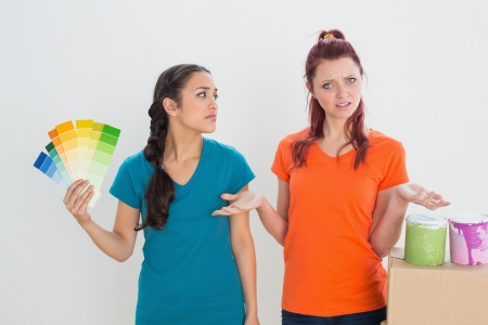 Two young confused female friends choosing color for painting a room against whitTwo young confused female friends choosing color for painting a room against white backgrounde background photo