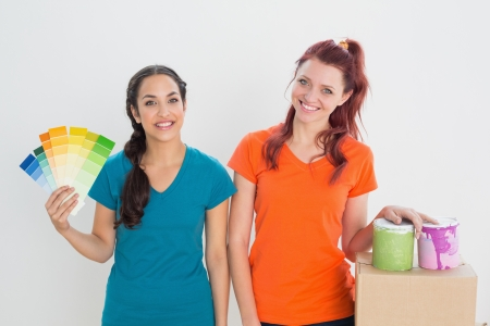 Portrait of two happy female friends choosing color for painting a room against white background photo