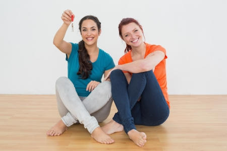 Portrait of two cheerful female friends with house keys sitting on the floor photo