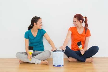 Two smiling female friends with brushes and paint can sitting in a new house photo