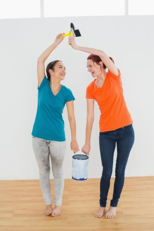 Full length of two cheerful female friends with brushes and paint can standing in a new house photo