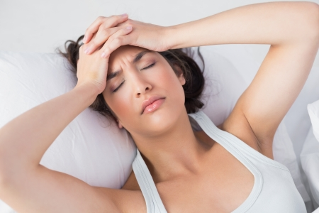 pounding head: High angle view of a sleepy young woman suffering from headache with eyes closed in bed at home