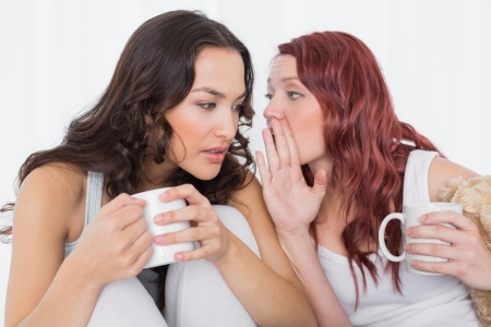 Relaxed young female friends with coffee cups gossiping in bed at home photo